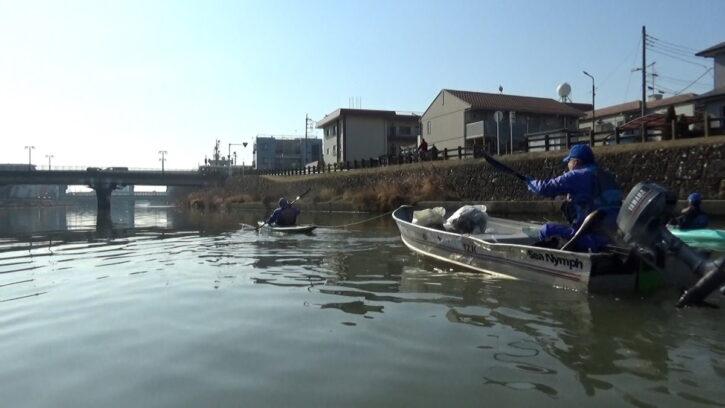 手漕ぎカヤックに曳航されるエンジンボート